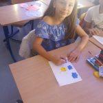 Uczennica siedzi w klasie przy ławce i rysuje