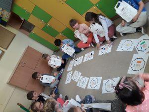 Dzieci przyglądają się ozobotom, które poruszają się wokół rąk, wody i mydła.