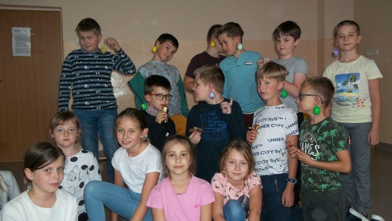 Uśmiechnięte dzieci prezentują upominki, które dostały z okazji Dnia Chłopca – na uszach – tak jak kolczyki - zawieszone mają kolorowe breloczki.