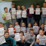 Uśmiechnięte dzieci z kl.3d prezentują samodzielnie ułożone puzzle z tabliczki mnożenia.