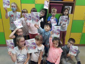 Dzieci pokazują kolorowanki, które dostały w prezencie.
