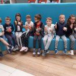 Dzieci siedzą , liżą lody i jedzą słodkości.