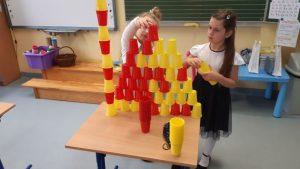 Dwie uczennice układają wieżę z żółtych i czerwonych plastikowych kubeczków.