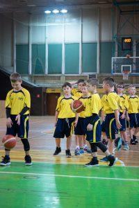 Chłopcy klasy sportowej stoją w rzędzie czekając na swoją kolej rzutu.