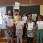 Dzieci pokazują obrazek pokolorowany według instrukcji.