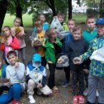 Uczniowie kl.3d wśród drzew prezentują zebrane dary jesieni znalezione w żorskim parku (liście, żołędzie, kasztany, kora drzewa, jarzębina)