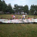 Dzieci z klasy 1c prezentują wykonane przez siebie obrazy łąki - odbitej na tkaninie.