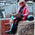 Zdjęcie przedstawia uczennicę siedzącą w stajni na sianie i czytającą książkę. W tle widać konia stojącego w boksie