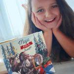 Zdjęcie przedstawia uśmiechniętą uczennicę przedstawiającą książkę Maja ratuje święta