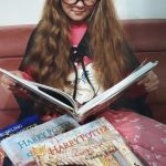 Zdjęcie przedstawia uczennicę w okularach czytającą książkę o przygodach Harrego Pottera