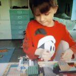 Chłopczyk buduje wioskę Świeętego Mikołaja z klocków lego.