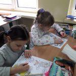 1c-Dziewczynki starannie kolorują postaci.
