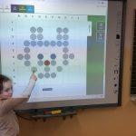 Na tablicy multimedialnej uczennica z klasy 1b prezentuje zakodowanego kotka.