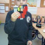 Uczeń z 3b prezentuje kolorowe serce z klocków lego.