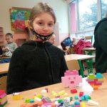Uczennica z klasy 3c prezentuje serce i kotka z klocków lego.