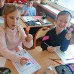 Dziewczynki kodują, kolorując kratki na odpowiednie kolory.
