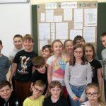 Grupa uczniów 3d stoi przed planszą z rozwiązanymi zadaniami.