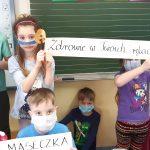 1b-Dzieci prezentują hasła na temat przestrzegania obostrzeń.