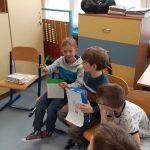 Chłopcy pokazują zawartość lekturowych pudełek.