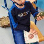 Chłopiec pokazuje gałązkę drzewa iglastego.