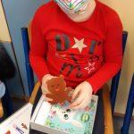 Dziewczynka pokazuje ozdobione pudełko rysunkiem, głównego bohatera Czarnego Noska.