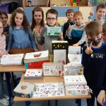 Uczniowie klasy 1b pokazują wykonane lekturowe pudełka.