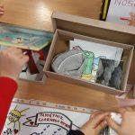Uczniowie klasy 1b pokazują wykonane lekturowe pudełka wraz z zawartością: plecak, serduszko.
