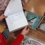 Uczennica pokazuje wykonane lekturowe pudełka wraz z zawartością: pamiętnik.