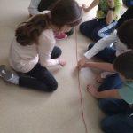 Uczniowie sprawdzają ile wynosi liczba Pi za pomocą włóczki.