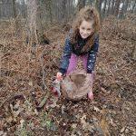dziewczynka zbierająca śmieci w lesie