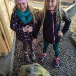 dziewczynki zbierające śmieci w lesie