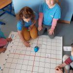Dziewczynki kodują drogę dla myszki-robota.