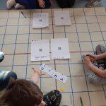 Uczniowie skanują kody QR odczytują zaszyfrowane hasło.