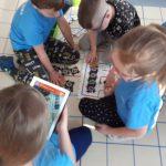 Dzieci układają z puzzli AR trasę dla ozobotów. Skanują puzzle AR. Na tablecie pojawia się wiosenny obraz.