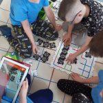 Dzieci układają z puzzli AR trasę dla ozobotów.