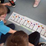 Dzieci obserwują zakodowaną trasę ozobotów.