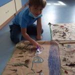 Chłopiec ustawia ozobota do pokonania zakodowanej, kolorowej trasy.