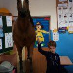 Chłopiec wskazuje konia. (rozszerzona rzeczywistość)
