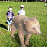 Chłopcy stoją za niedźwiedziem 3d.