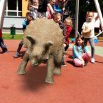Uczniowie na placu zabaw z dinozaurem.