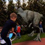 Zabawy dzieci z dinozaurem.