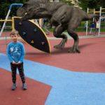 Uczennica pozuje do zdjęcia w tle plac zabaw i dinozaur-rozszerzona rzeczywistość.