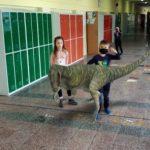 Zabawy na korytarzu szkolnym z dinozaurem.