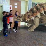 Dzieci próbują głaskać dinozaura.