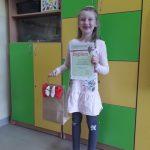 Laureatka z klasy 1c, Emilia Maciołek prezentuje nagrodę.