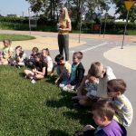 Uczniowie siedzą na trawie i słuchają Pana policjanta.