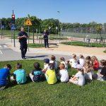 Uczniowie siedzą na trawie. Policjant prowadzi pogadankę.