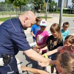 Policjant wręcza dzieciom odblaski na ręce.