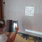 Zabawa kodami QR. Dziewczynka skanuje kod.