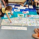 Uczniowie prezentują trasy ozobotów w morskiej scenerii.